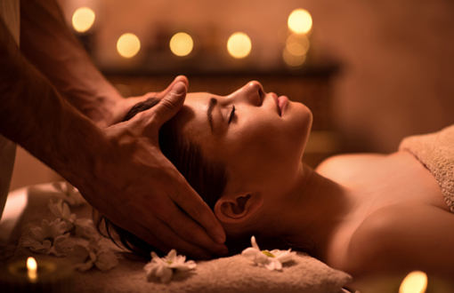 Relaxed woman receiving head massage at spa.
