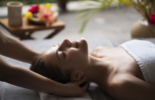 Smiling woman relaxing during her massage treatment at the spa.