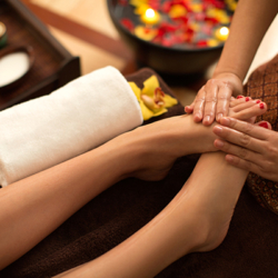 Young woman enjoying foot massage in Thai SPA.